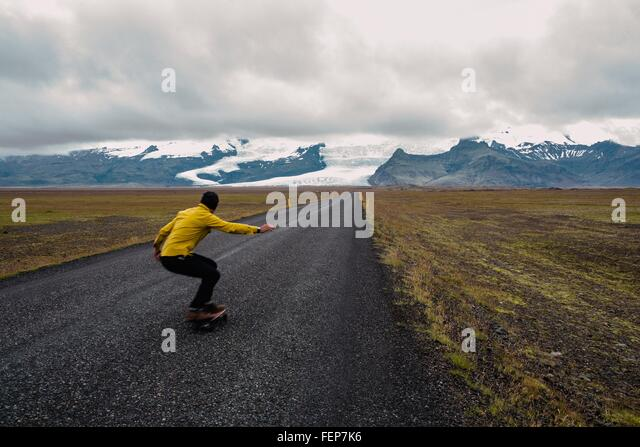 Rear view of mid adult man skateboarding to snow covered mountain range, Iceland - Stock Image
