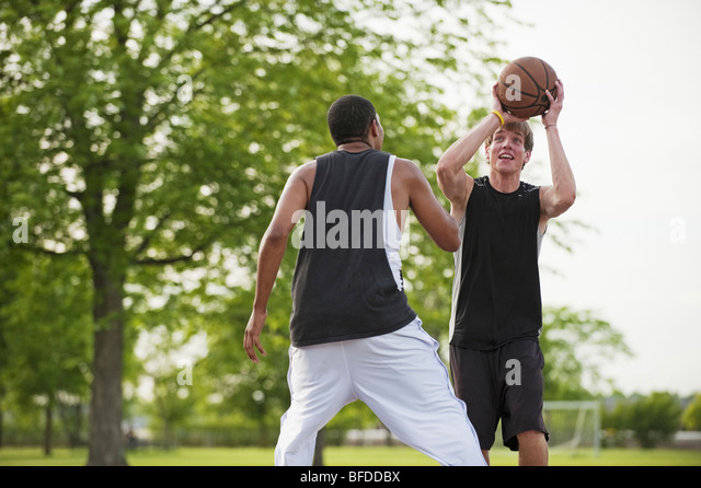 Two young men play one on one Basketball at Barstow Park in Vermillion, South Dakota. - Stock Image