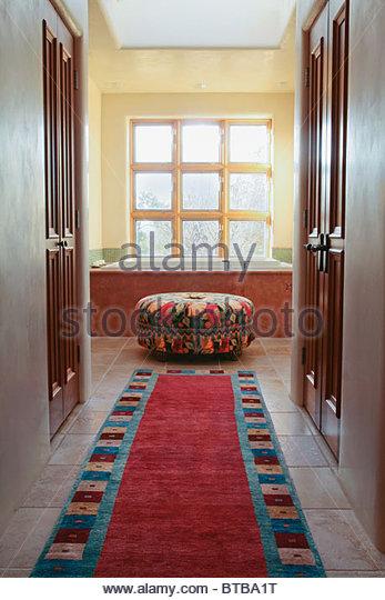 Carpet runner leading down hall into bathroom - Stock-Bilder