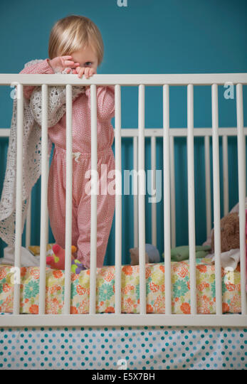 Portrait of female toddler hiding behind comfort blanket in crib - Stock Image