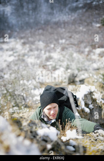 A man hiking in the mountains climbing up a steep rock face. - Stock Image