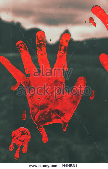 Grimy horror scene of red halloween hand print stained on countryside window. Pressing terror - Stock Image