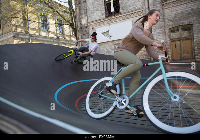 Male and female cyclists racing downhill on city velodrome, Riga, Latvia - Stock Image