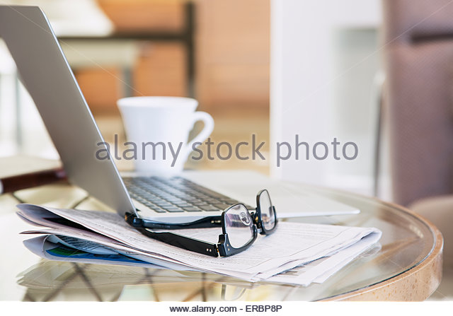Eyeglasses and newspaper next to laptop and coffee - Stock-Bilder