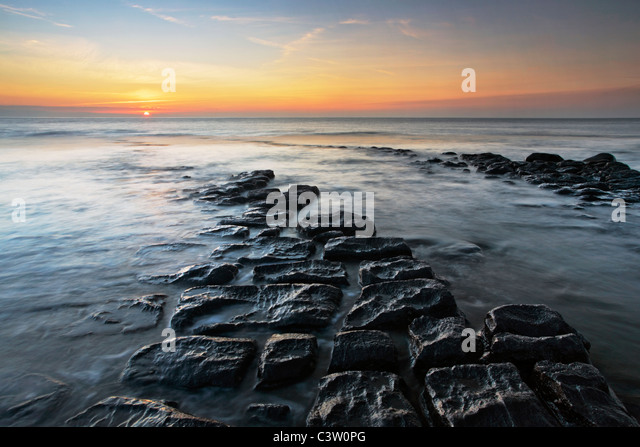 Sunset over the Bristol Channel as seen from the dramatic rocky shores of Nash Point in Southern Wales - Stock Image