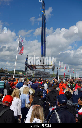 People gather and show great curiosity when Swedish America's Cup  72 class catamaran is lifted for wing sail - Stock Image
