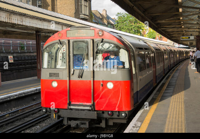 A driver on a Piccadilly Line train at Barons Court tube station, London, UK - Stock Image