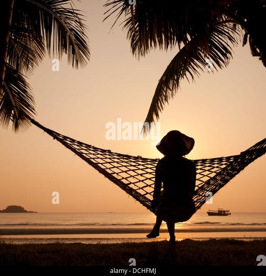 woman in hammock enjoying sunset on the beach - Stock Image