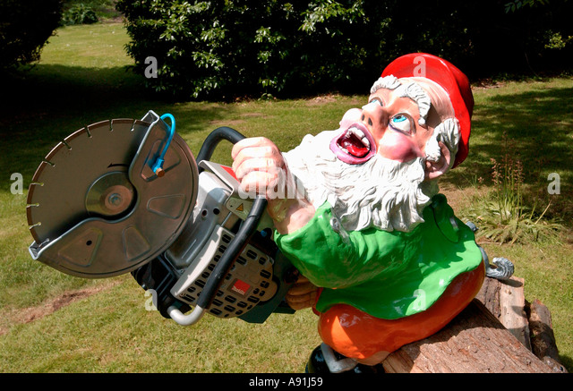 Garden gnome with a chainsaw - Stock Image