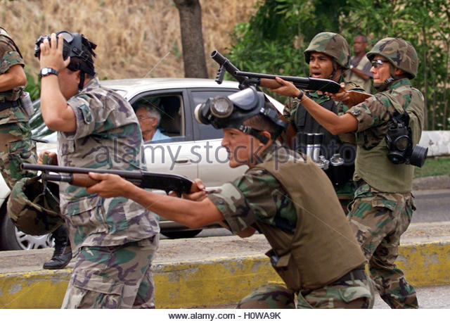 National guardsmen shoot tear gas at protesters in Caracas April 26,  2003. Venezuelan troops and police fired tear - Stock Image