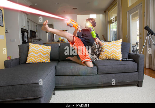 Young boy on sofa, wearing virtual reality headset, kicking leg, firing laser guns, digital composite - Stock-Bilder
