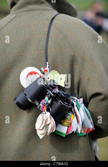 A horse racing enthusiasts binoculars with meeting badges attached UK - Stock Image