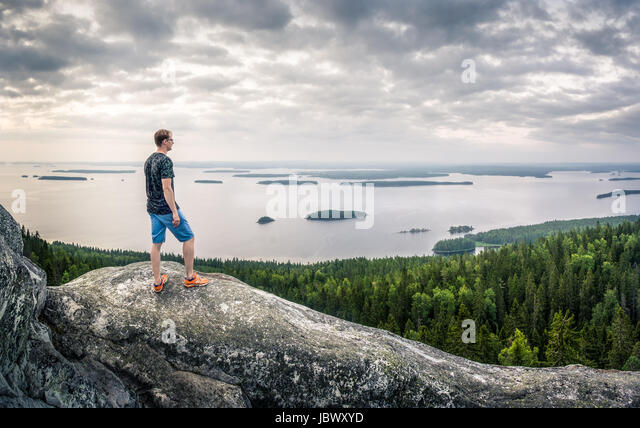 Scenic landscape with lake and sunset at evening in Koli, national park. Finland. Hiker standing in the front. - Stock Image