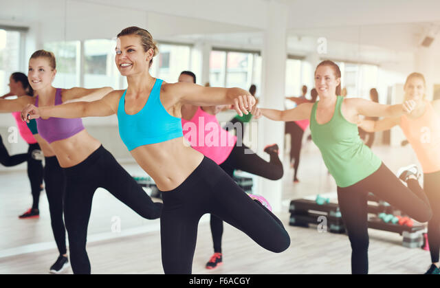 Young women in colorful sportswear working out in aerobics class at the gym with focus to a smiling slender lady - Stock Image
