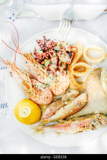 Cooked seafood on plate with lemon and wine - Stock Image