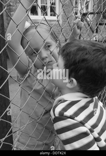 A child kissing another child in black and white - Stock Image
