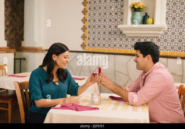 Hispanic man proposing marriage to woman in restaurant - Stock Image