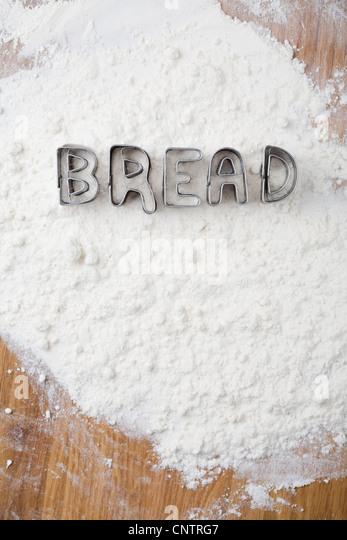 Cookie cutters spelling bread in flour - Stock Image