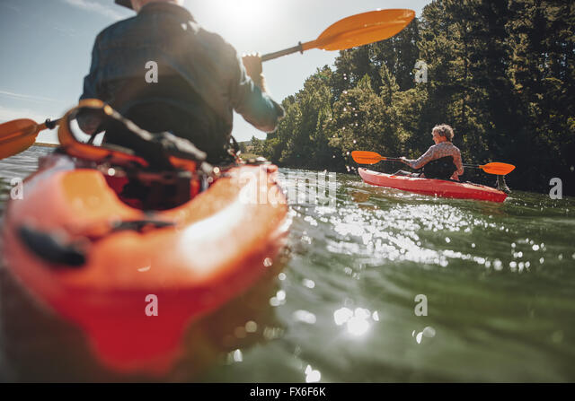 Portrait of mature woman kayaking in lake on a sunny day. Couple canoeing in a lake on  summer day. - Stock Image