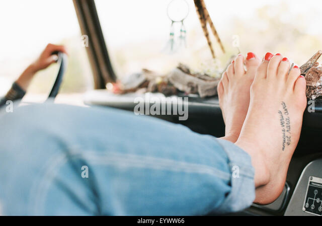 Barefoot woman resting her feet on the dashboard of a 4x4, a tattoo on her right foot. - Stock-Bilder