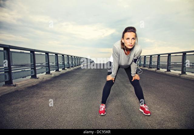 Focused runner outdoors resting on the bridge - Stock Image