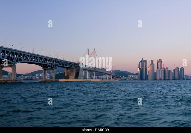 Residential buildings and hotels in Haeundae, Busan, South Korea and Gwangan Bridge at dusk, seen from the sea. - Stock Image