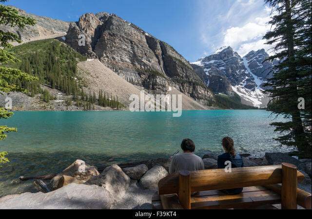 Two people sitting by Moraine Lake, Banff National Park, Canadian Rockies, Alberta, Canada - Stock Image