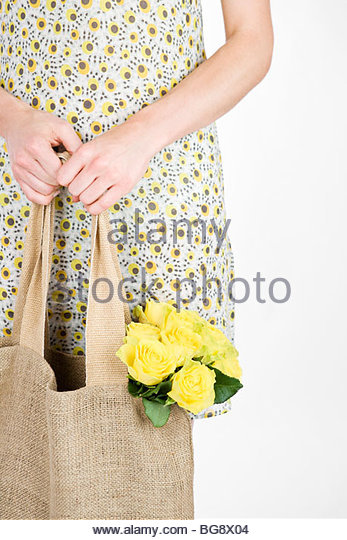 A Young Woman Carrying A Bunch Of Yellow Roses In A Shopping Bag - Stock Image