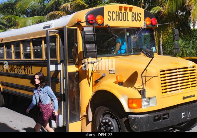 Miami Beach Florida school bus girl student getting off - Stock Image