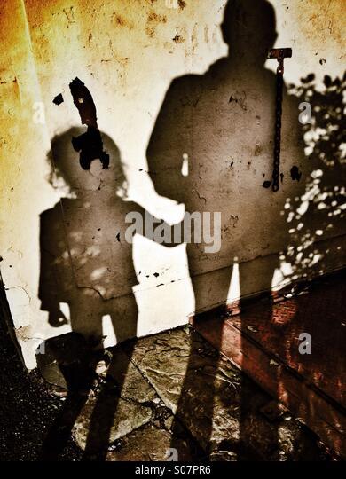 Shadow on peeling wall of man and young girl - Stock Image
