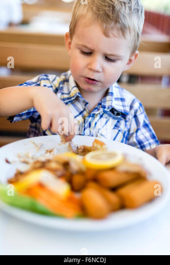 Cute child eating alone with hands - Stock Image