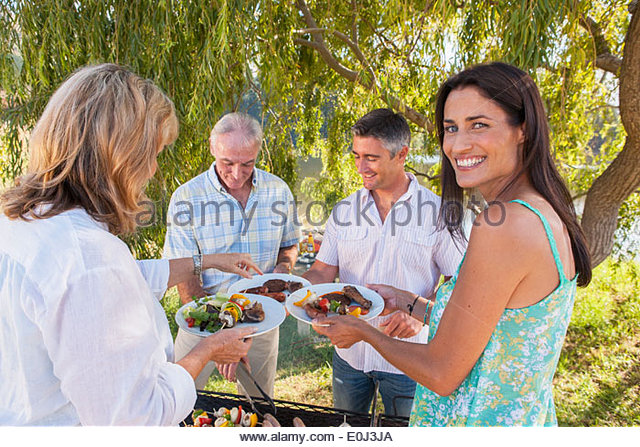 Adult Family Group Cooking Barbeque In Countryside - Stock-Bilder