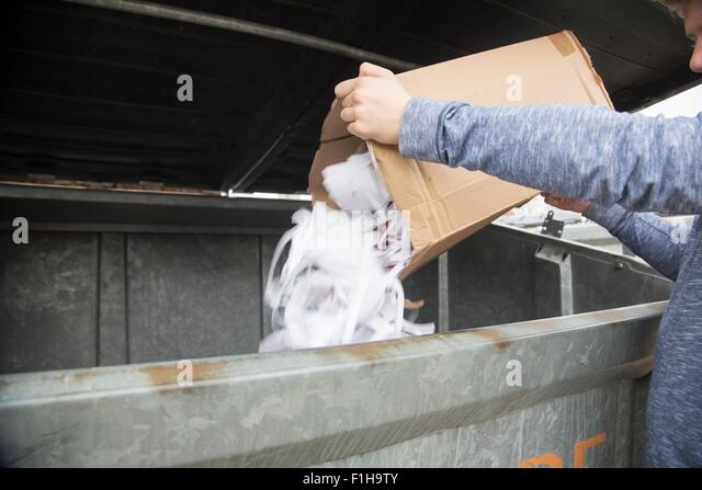 Teenage boy emptying paper waste to recycling bin - Stock Image