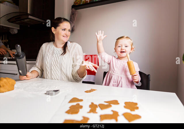 Happy mother and daughter enjoying while making cookies at table - Stock-Bilder