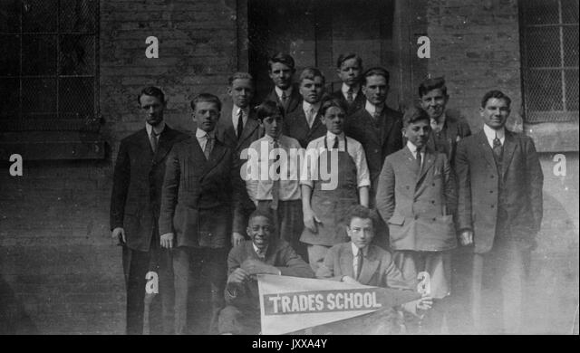 Full length landscape shot of a small group of schoolboys, two seated holding a sign that says 'Trades School' - Stock Image