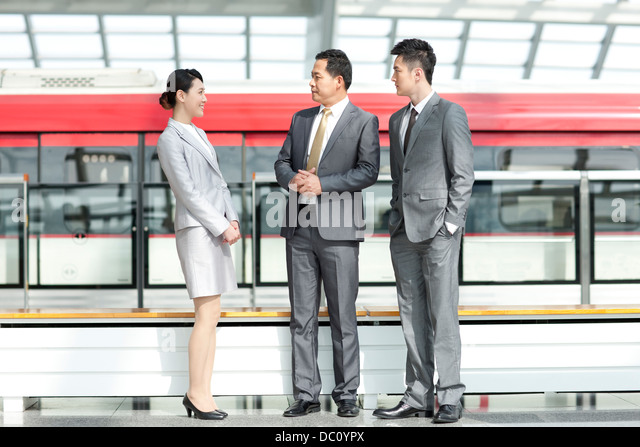 Business persons talking at subway station - Stock Image