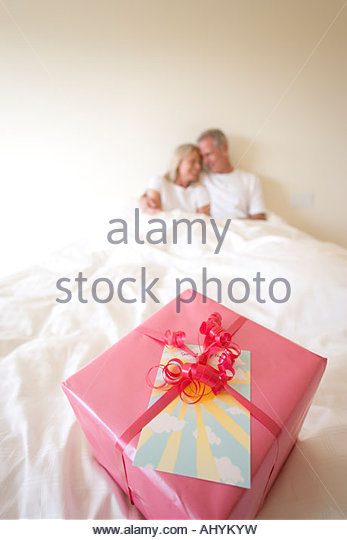 Mature couple sitting upright in bed, focus on birthday gift wrapped in pink wrapping paper and red ribbon in foreground - Stock Image