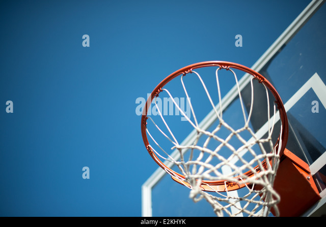 An orange basketball hoop with a transparent backboard with net against a clear blue sky. - Stock Image