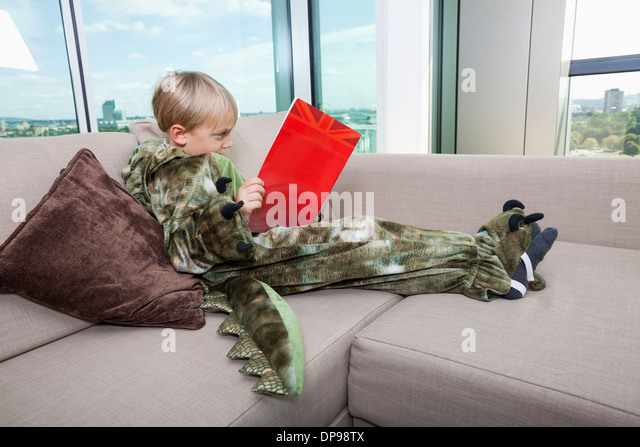 Boy in dinosaur costume reading story book on sofa at home - Stock Image