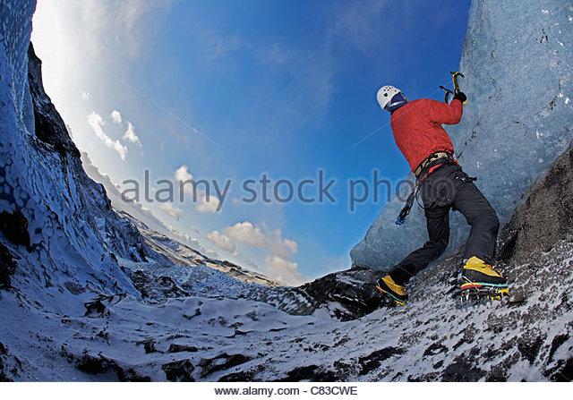 Man climbing glacier with ice picks - Stock Image
