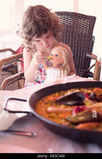 Girl sitting at dinner table pretending to feed her doll - Stock Image