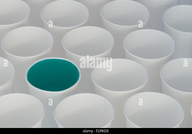 White paper cups on a white background. Some cups have colored liquid in them - Stock Image