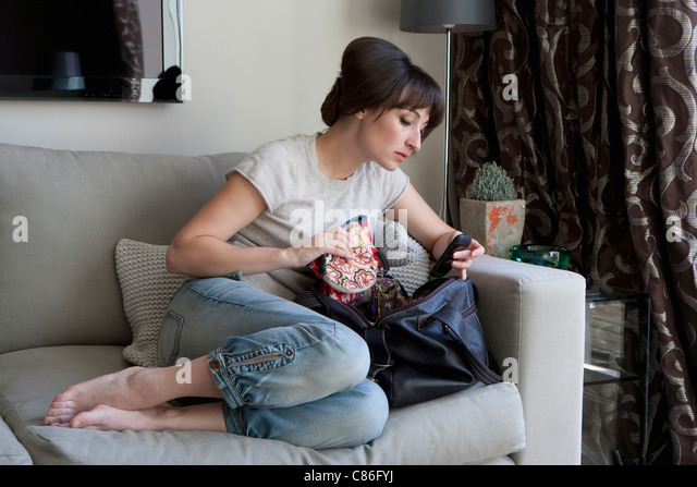 Woman searching contents of purse - Stock Image