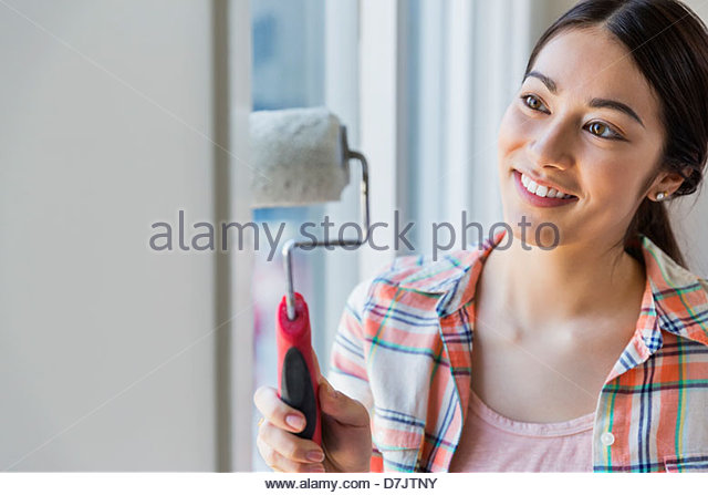 Young woman painting wall at home - Stock Image