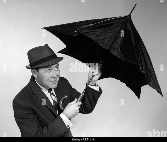 1960s BUSINESSMAN OPENING UP UMBRELLA - Stock Image
