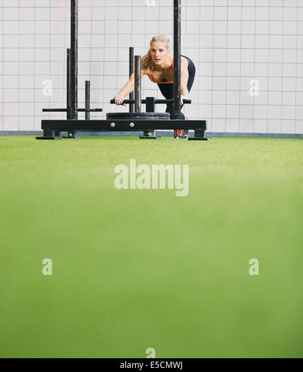 Strong young woman pushing the prowler on artificial grass turf. Fit female using prowler exercise equipment at - Stock Image