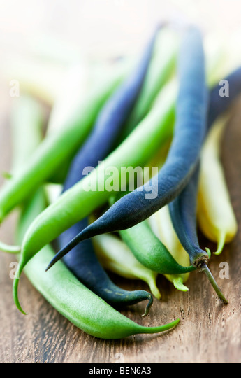 Pile of purple yellow and green string beans on cutting board - Stock Image