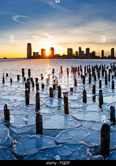 Wood pilings from New York old pier sticking out through the ice on Hudson River at sunset with Jersey City buildings - Stock Image