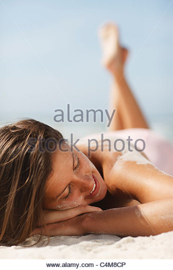 Woman sunbathing on beach - Stock Image