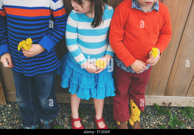 Three children standing in a row, holding flowers - Stock Image